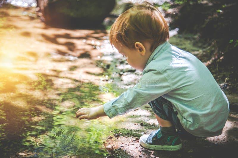 Мальчик малыша в природе около воды стоковые фотографии rf