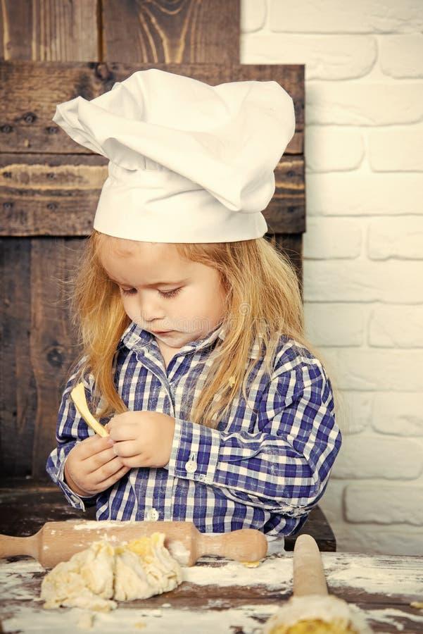 Мальчик малыша в шляпе шеф-повара и тесте муки замешивая стоковое изображение rf