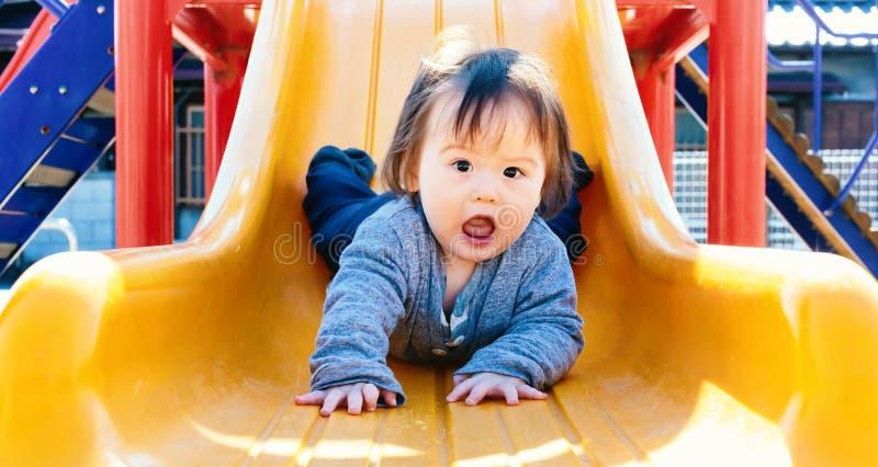 Мальчик малыша играя на спортивной площадке стоковое фото