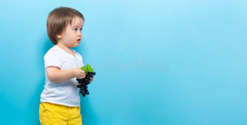 Мальчик малыша с виноградинами стоковая фотография