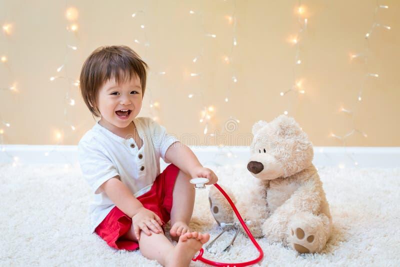 Мальчик малыша с доктором плюшевого мишки стоковая фотография