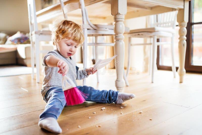 Мальчик малыша с щеткой и dustpan дома стоковое фото rf