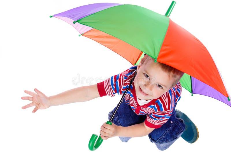 мальчик меньший сидя зонтик вниз стоковое фото rf