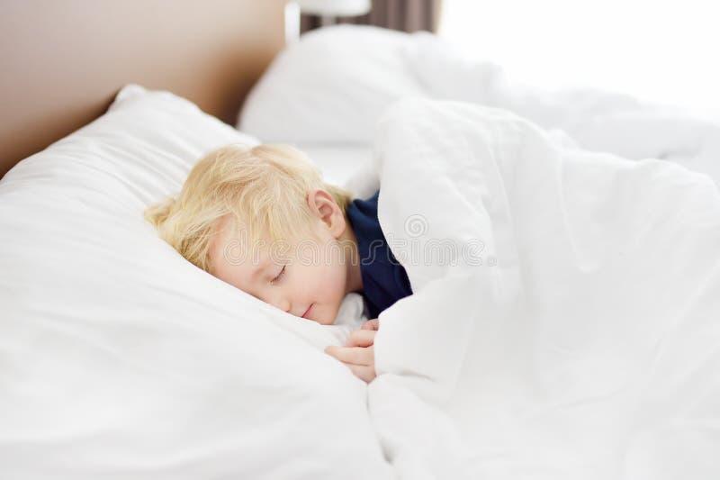 мальчик милый немногая Утомленный ребенок принимая ворсину в родительской кровати ` s стоковые изображения rf