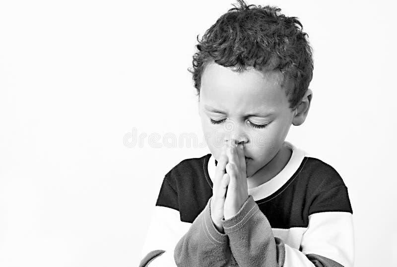 Мальчик моля с его руками обхваченными совместно стоковые фотографии rf