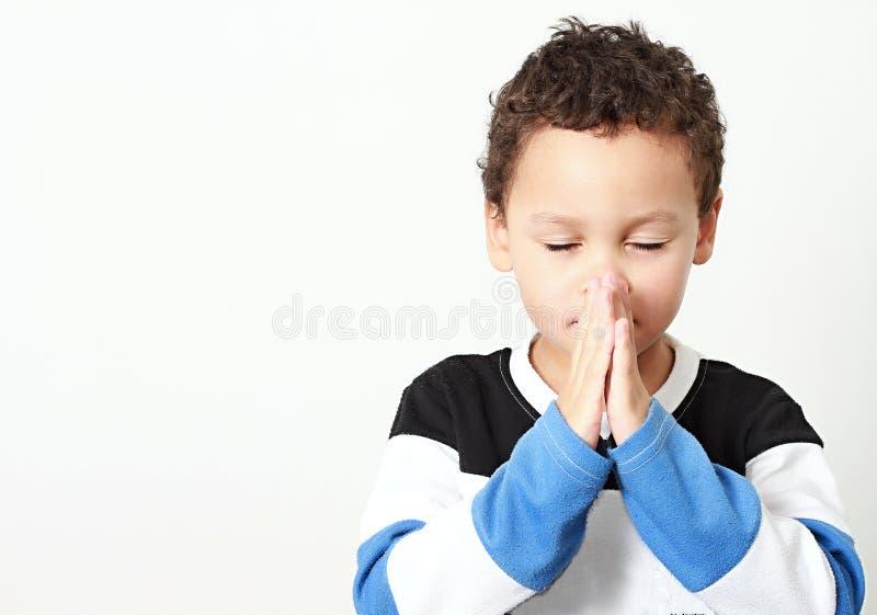 Мальчик моля с его руками обхваченными совместно стоковая фотография rf