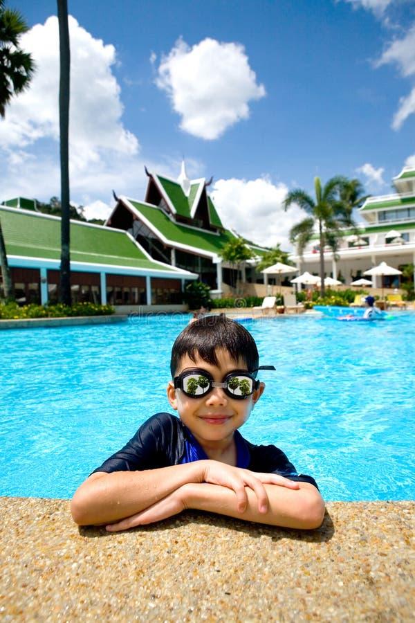 мальчик наслаждаясь детенышами заплывания бассеина стоковое фото rf