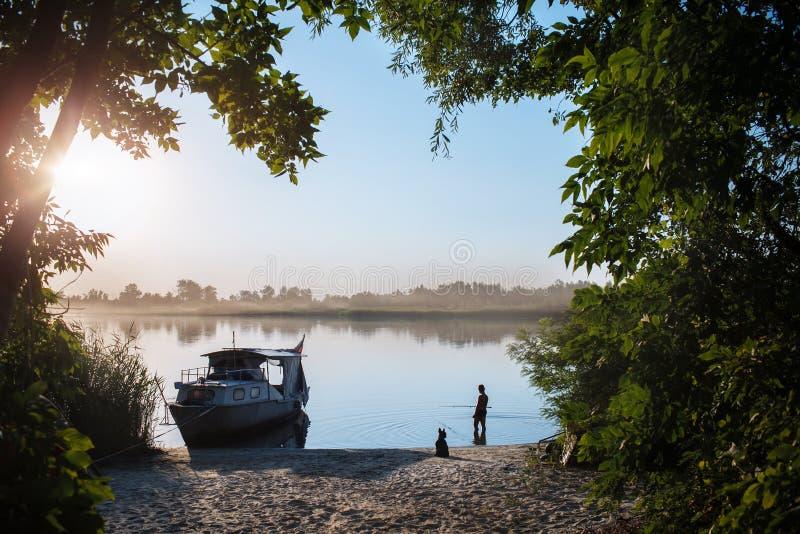 Мальчик на восходе солнца улавливает рыб стоковое фото rf