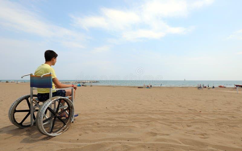 Мальчик на инвалидной коляске смотрит на море стоковое изображение rf