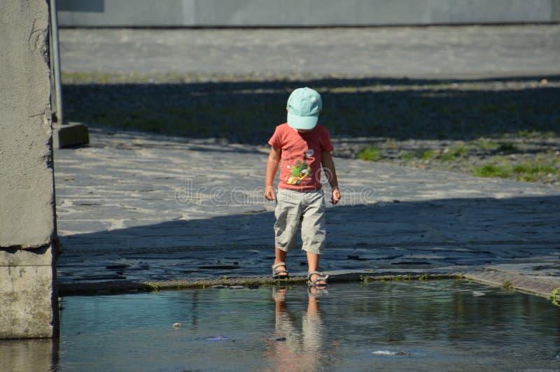 Мальчик на лужице воды стоковое фото rf