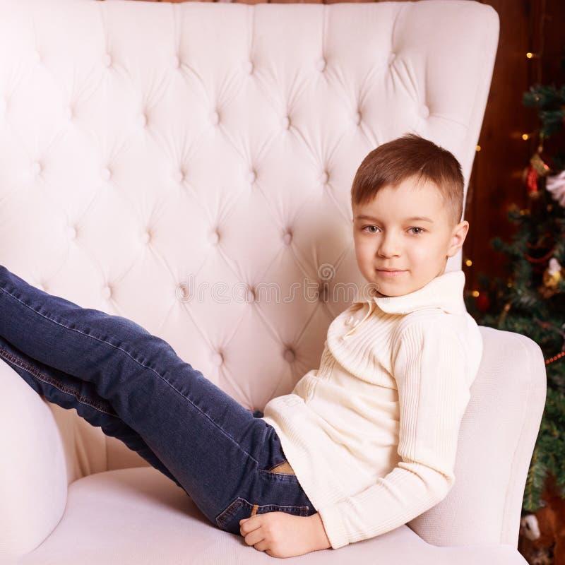 Мальчик на стуле Интерьер рождества абстрактный коричневый цвет предпосылки выравнивает изображение горизонтально стоковые изображения