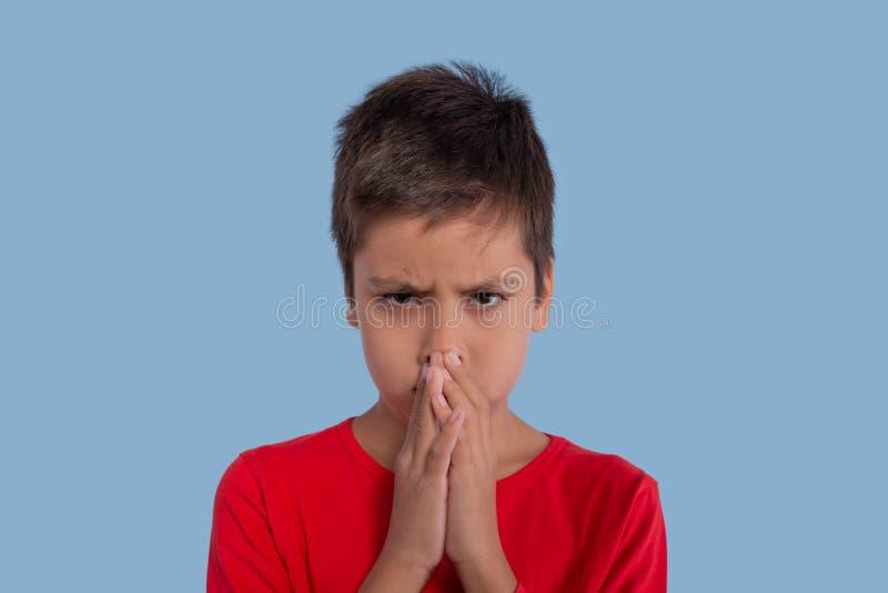 Мальчик нося красную рубашку очень расстроен или сердит на задней части сини стоковые фото