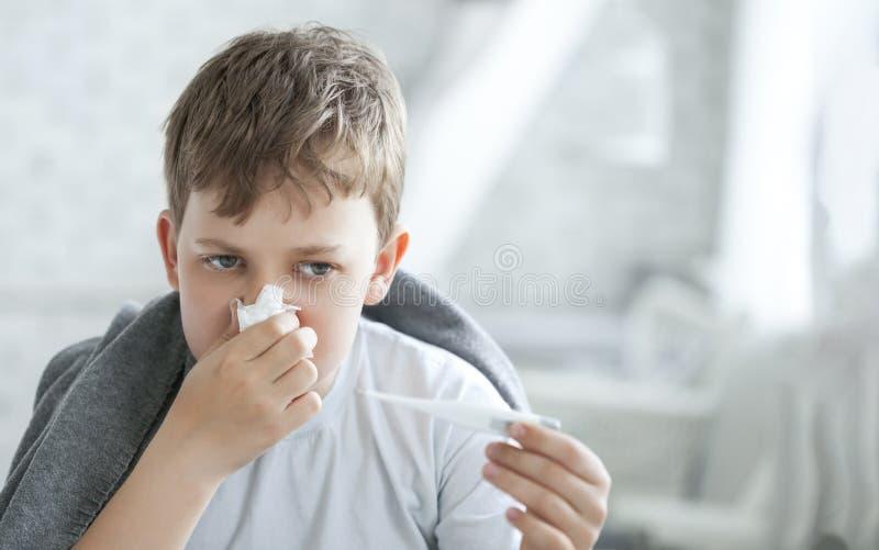 Мальчик обтирает его нос с тканью стоковые фото