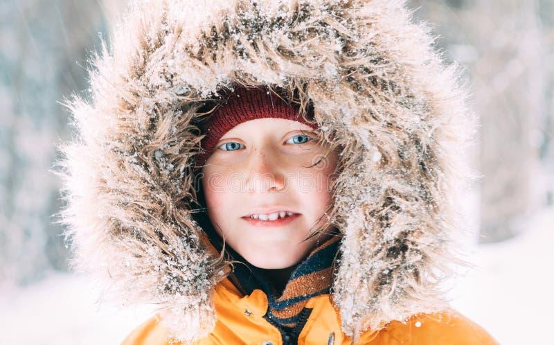 Мальчик одетый в теплом с капюшоном случайном Outerwear куртки Parka идя в портрет стороны снежного леса жизнерадостный усмехаясь стоковое фото