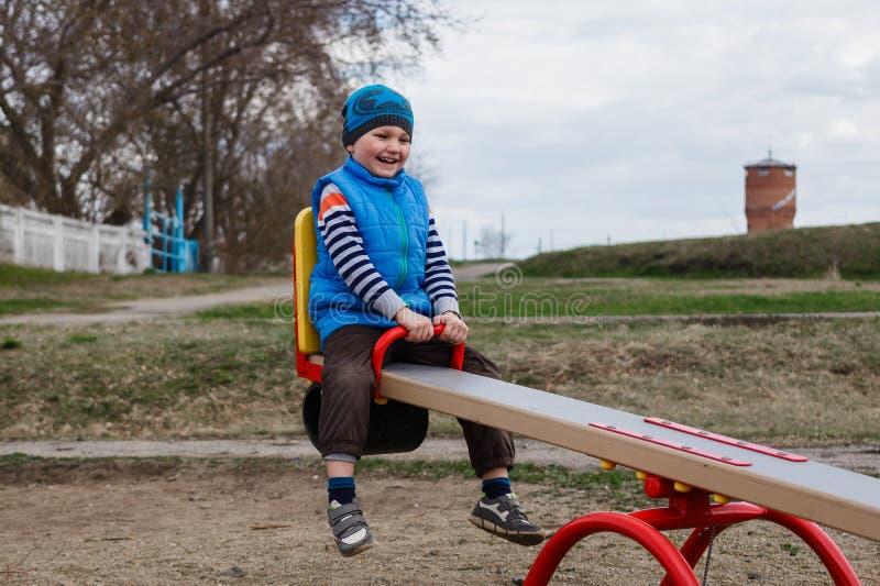 Мальчик отбрасывая на качании на спортивной площадке весной стоковое фото rf