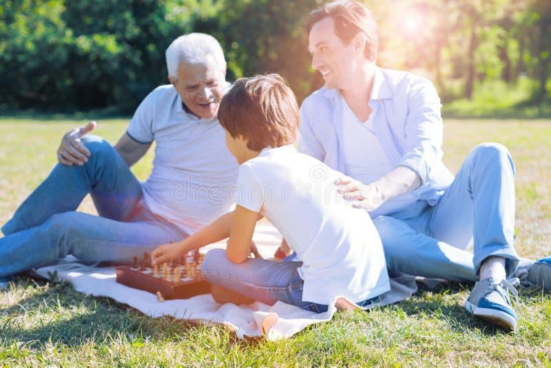 Мальчик отца и дедушки уча играя шахмат стоковые фотографии rf