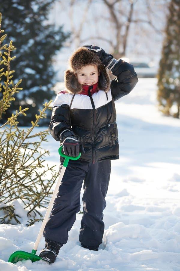Мальчик очищает снежок стоковое фото rf