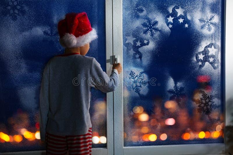 Мальчик перед рождеством около окна с снежинками стоковое фото