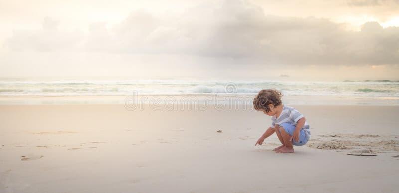 мальчик пишет на пляже с белым песком стоковое изображение rf