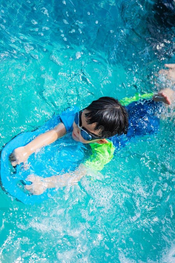 Мальчик плавает с изумленными взглядами kickboard и плавания стоковые изображения