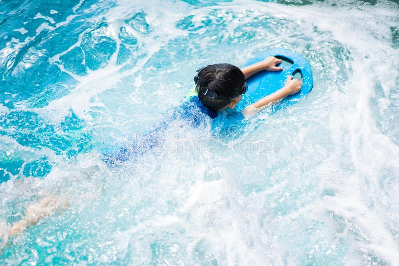 Мальчик плавает с изумленными взглядами kickboard и плавания стоковая фотография