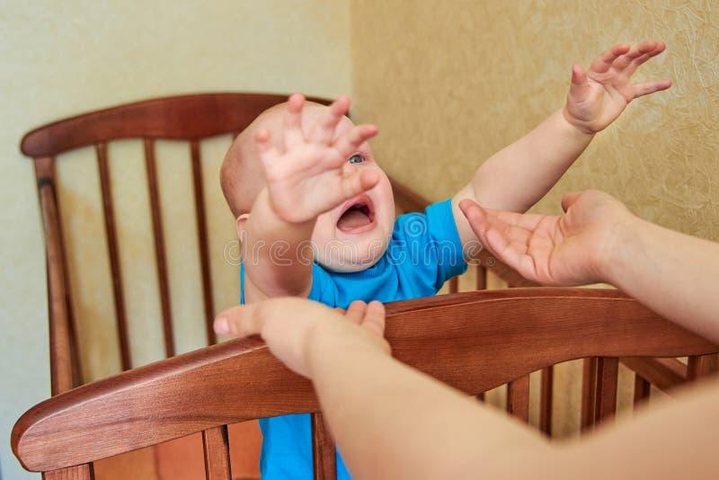 Мальчик плачет в шпаргалке и вытягивает его руки к маме стоковые фото