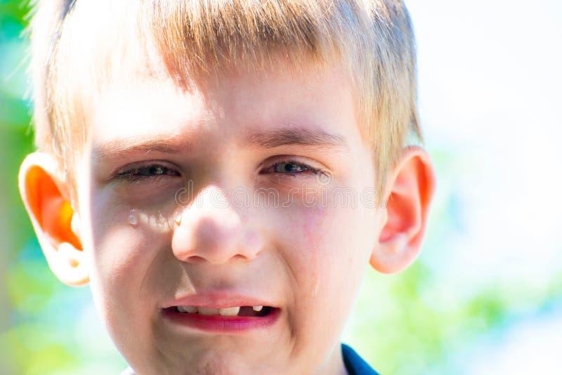 Мальчик плачет разрывы в дневном времени на улице и потребности жалеют, конец-вверх стоковые фото