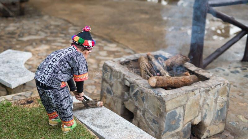 Мальчик племени холма сделать лагерный костер для предотвращения холода стоковые фото