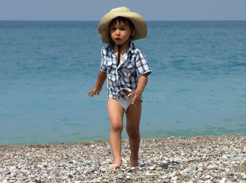 мальчик пляжа немногая гуляя стоковые фото