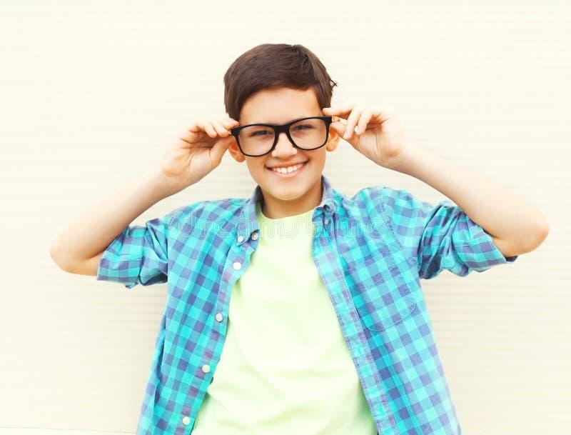 Мальчик подростка портрета счастливый усмехаясь в стеклах нося checkered рубашку стоковое фото