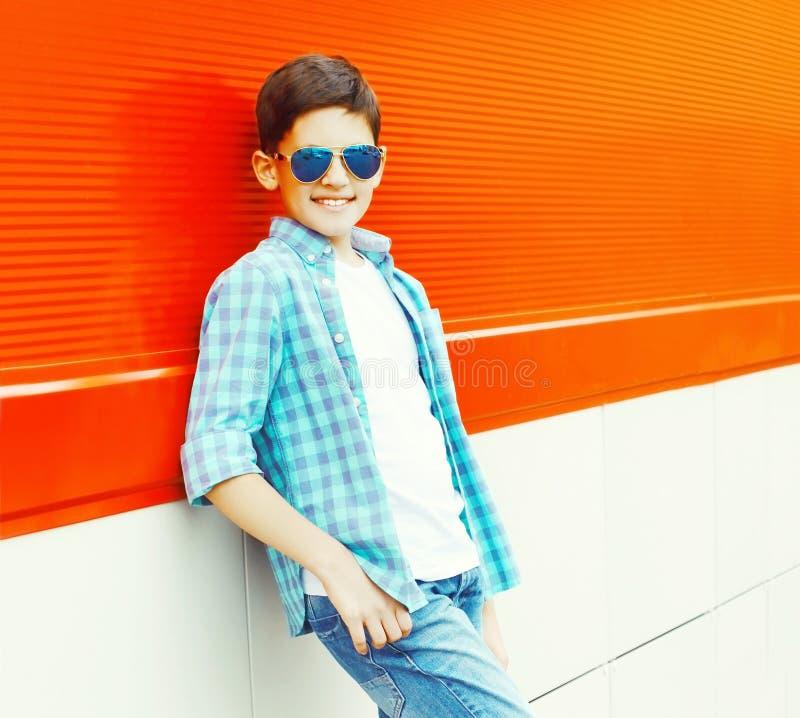 Мальчик подростка портрета усмехаясь в солнечные очки на красочном стоковые фото