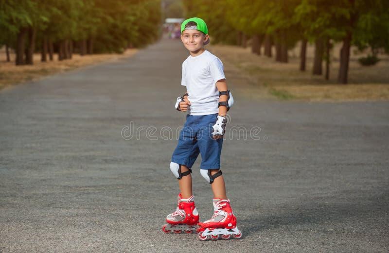 Мальчик положил дальше защитные пусковые площадки и коньки колена в парк стоковое фото