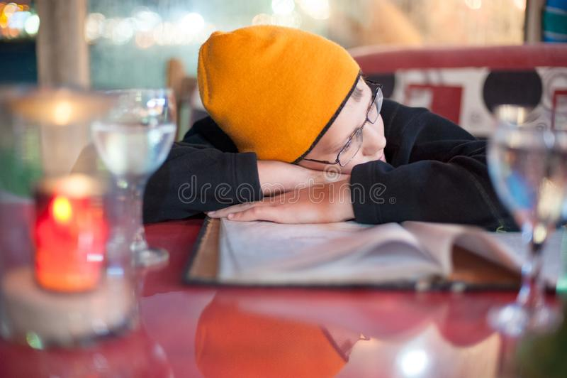 Мальчик положил его голову в его руки в кафе ждать заказ стоковая фотография