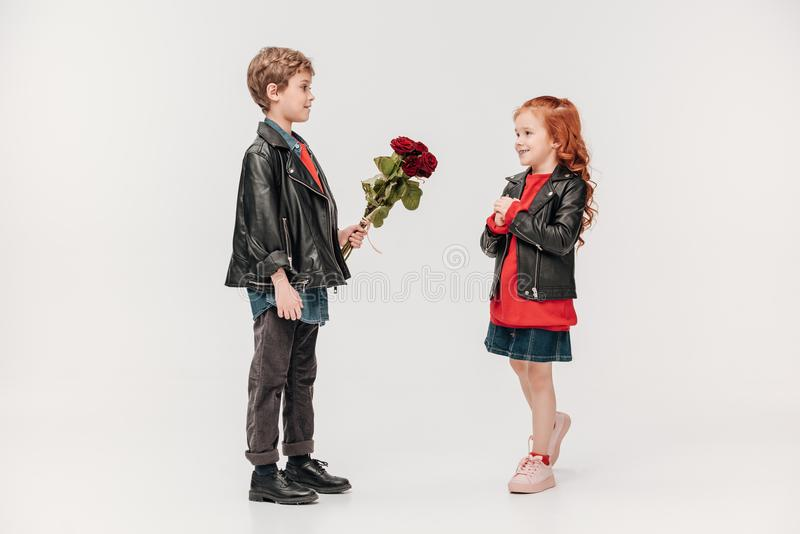 мальчик представляя розам букет к его красивой маленькой подруге стоковые фотографии rf