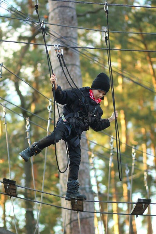 Мальчик преодолевая полосу препятствий в внешнем парке веревочки стоковое фото