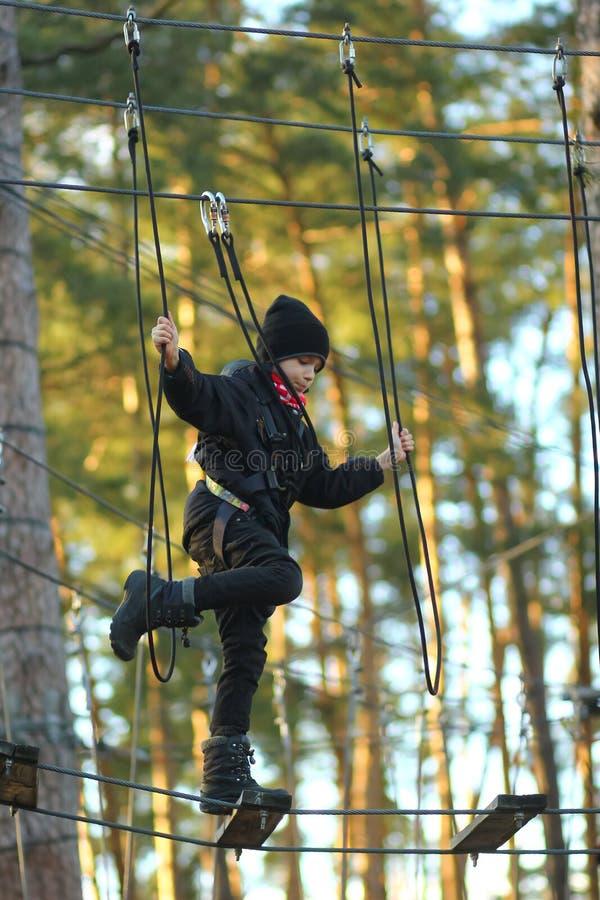 Мальчик преодолевая полосу препятствий в внешнем парке веревочки стоковое фото rf