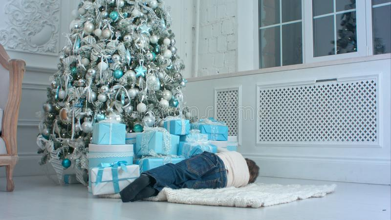 Мальчик претендуя спать на ковре рядом с рождественской елкой стоковые изображения rf
