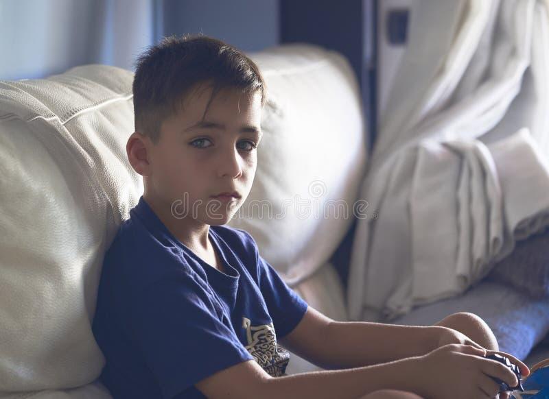 Мальчик при красивые зеленые глаза играя видеоигры стоковое фото