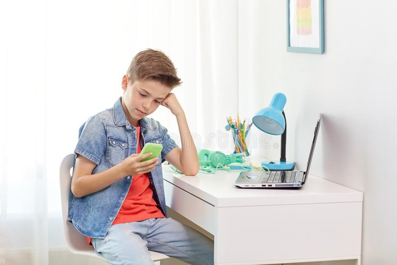 Мальчик при smartphone будучи задиранным текстовым сообщением стоковые изображения rf