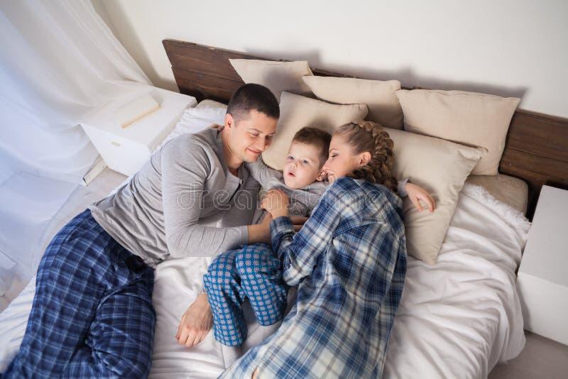 Мальчик проспал вверх в утре спать в спальне родителей стоковое изображение rf
