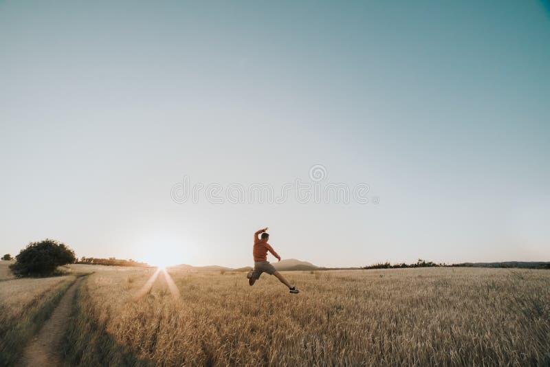 Мальчик прыгает на пшеничном поле на закате рядом с солнцем и x27;s стоковое фото