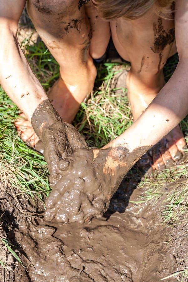 Мальчик работая и играя в грязи стоковая фотография