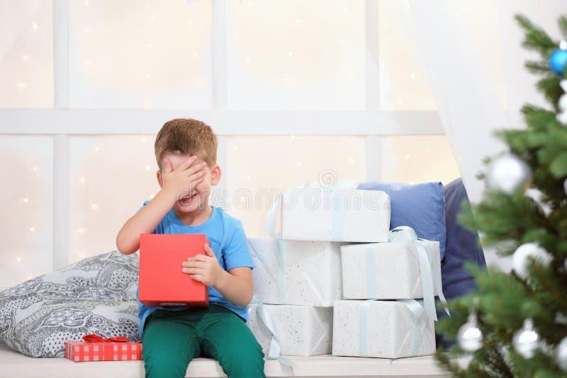 Мальчик раскрывает коробку с подарком на рождество стоковое изображение