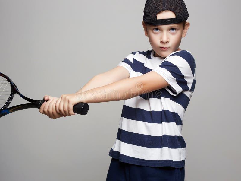 Мальчик ребенка играя теннис Дети спорта стоковое фото