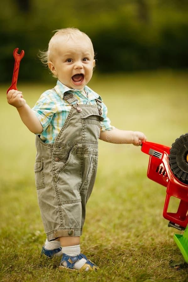 Мальчик ремонтирует автомобиль игрушки стоковое изображение