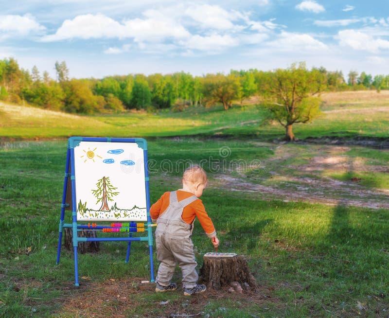 Мальчик рисует на холсте бумаги на мольберте на фоне живописной природы стоковые фото