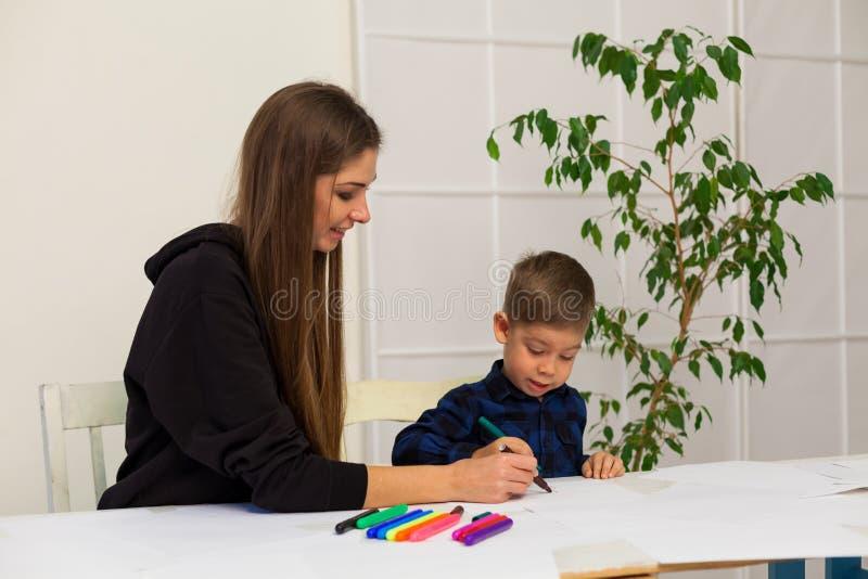 Мальчик рисует отметки от матери урока стоковое фото