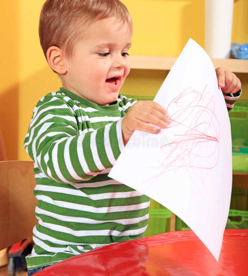 Мальчик самолюбиво показывает его собственн-нарисованное изображение стоковые изображения rf