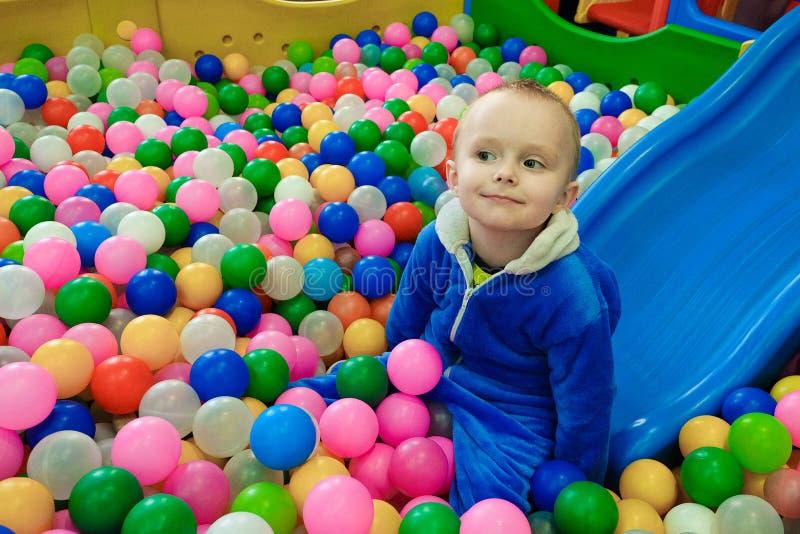 Мальчик свернул вниз скольжение в шарики пестротканой игры пластиковые стоковые фото