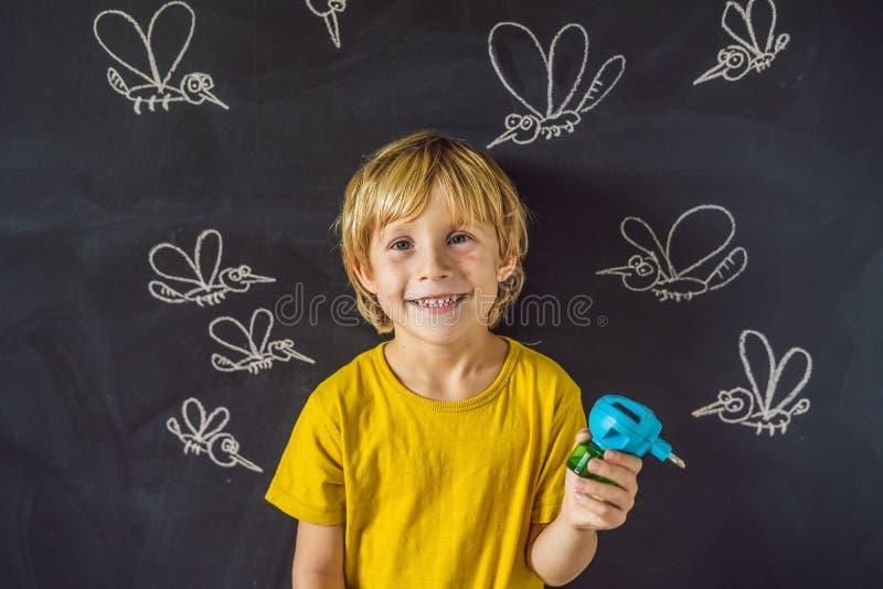 Мальчик сдержан москитами держа fumigator на темной предпосылке На классн классном с покрашенным мелом стоковые изображения rf